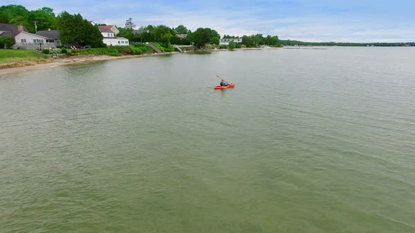 Lone middle age kayaker paddling out into vast lake, aerial view. Royalty-free stock video