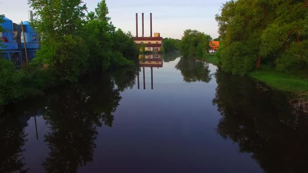 Factory with three smoke stacks reflecting in tranquil river, strangely beautiful cinematic view. Royalty-free stock video