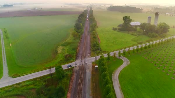Train rolling through foggy countryside at dawn, aerial perspective. Royalty-free stock video