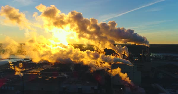Factory emissions from smokestacks backlit in the sunrise, moving aerial view. Royalty-free stock video