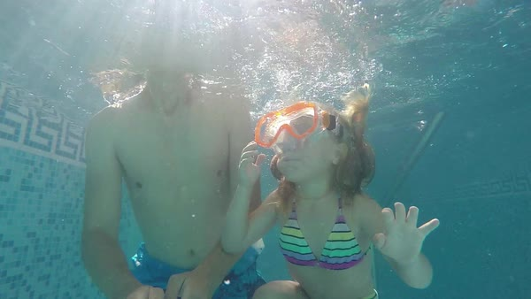 Father and daughter in swimming masks under water raised thumbs up, slow motion Royalty-free stock video