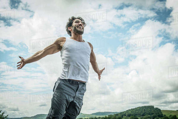 A bearded man leaping into the air on the shore beside Bala Lake in Wales Royalty-free stock photo
