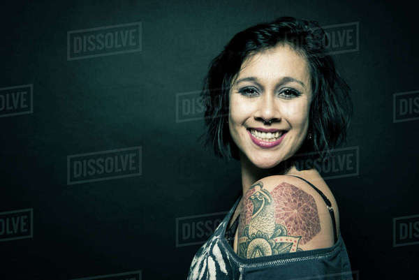 Studio portrait of a woman with a tattoo on her shoulder Royalty-free stock photo
