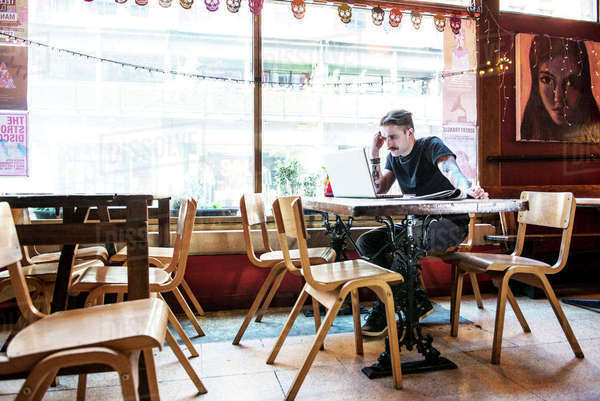 A young man sitting at a table in a coffee shop in Manchester Royalty-free stock photo