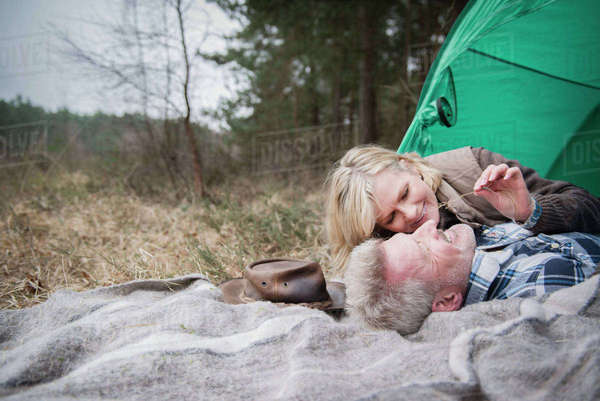 Senior couple cuddling together on a blanket at their campsite Royalty-free stock photo