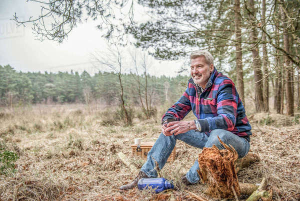 Senior man sitting enjoying the wilderness from his campsite Royalty-free stock photo