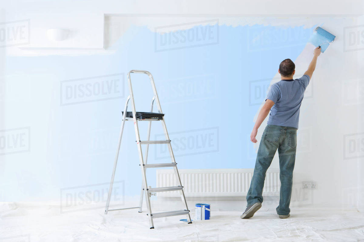 Man Painting Wall With Paint Roller Near Ladder Stock Photo