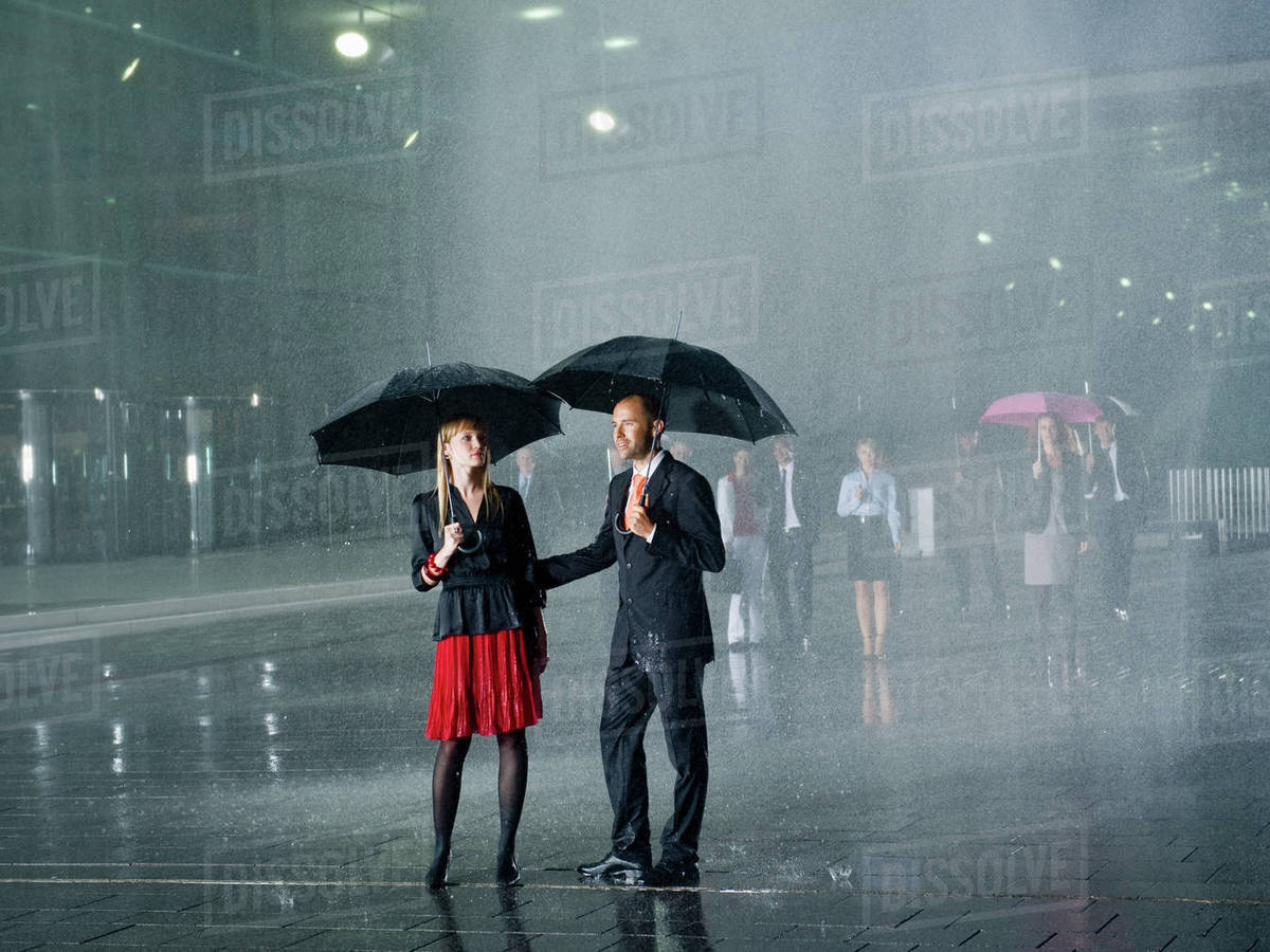 a couple standing in the rain under umbrellas stock photo dissolve