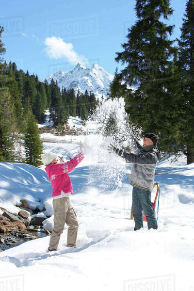 Playful couple throwing snow in woods below mountain Royalty-free stock photo