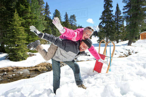 Portrait of man balancing woman on back in snowy woods Royalty-free stock photo