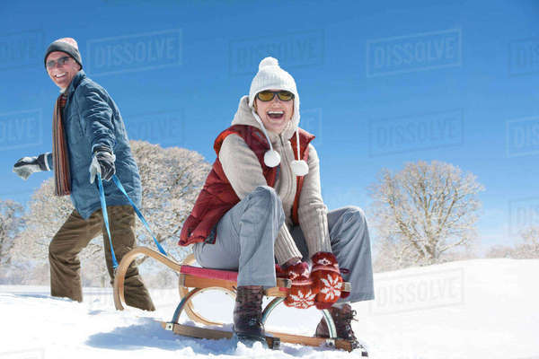 Portrait of smiling senior couple sledding in snowy field Royalty-free stock photo