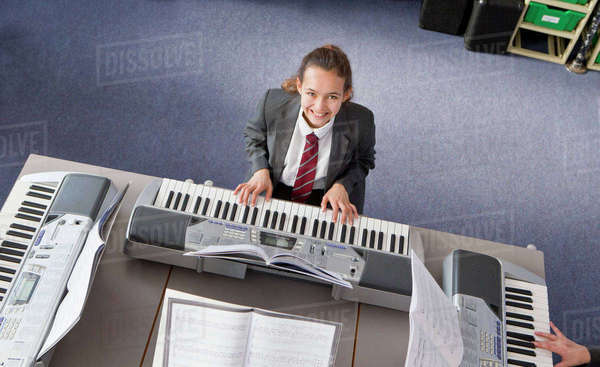 Portrait smiling high school student playing piano in music class Royalty-free stock photo