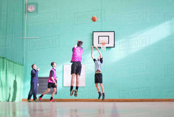 Gym teacher teaching high school students playing basketball in gym class Royalty-free stock photo