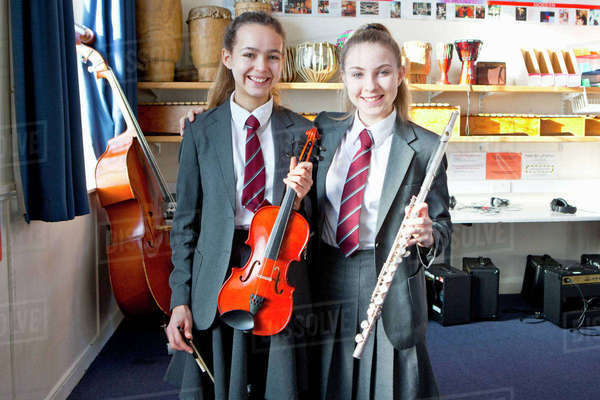 Portrait confident high school students holding violin and flute in music classroom Royalty-free stock photo