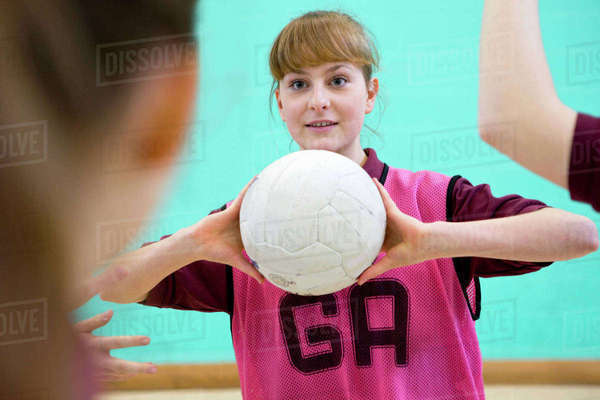 High school student playing netball in gym class Royalty-free stock photo