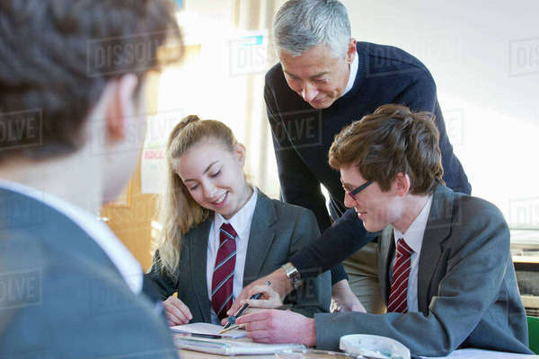 Teacher helping high school students doing homework in classroom Royalty-free stock photo