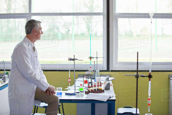 Pensive chemistry teacher looking out science classroom window Royalty-free stock photo