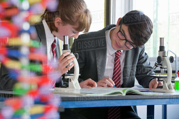 High school student conducting scientific experiment with helix DNA model in foreground Royalty-free stock photo