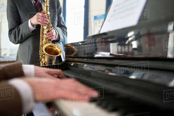 Close-up music teacher playing piano with high school student playing saxophone in background Royalty-free stock photo