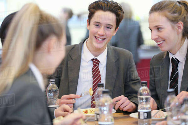 Smiling high school students eating lunch and talking in school cafeteria Royalty-free stock photo