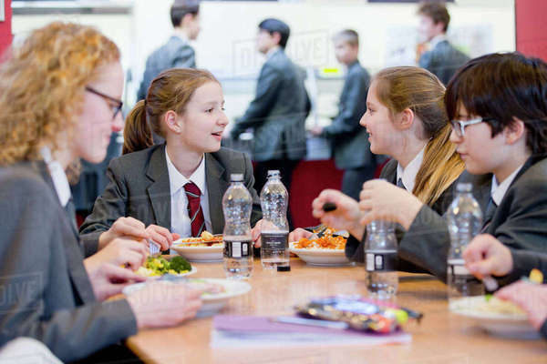 Middle school students eating lunch and talking in school cafeteria Royalty-free stock photo