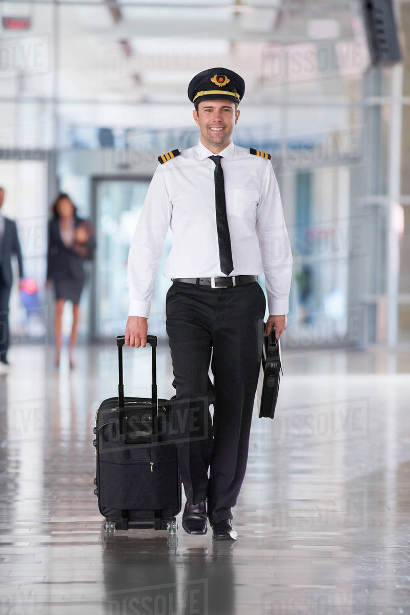portrait of airline pilot walking through airport lounge stock
