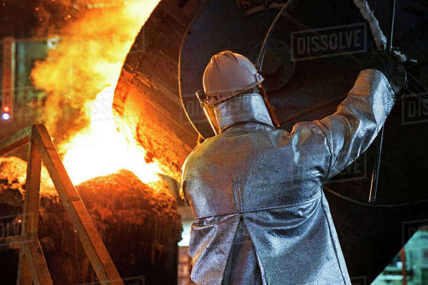 Worker in protective clothing pouring molten metal in foundry Royalty-free stock photo
