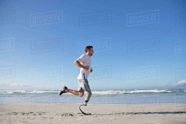Man with blade style artificial leg running along beach Royalty-free stock photo