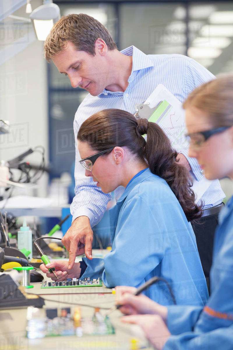 supervisor training technician to solder circuit board on productionsupervisor training technician to solder circuit board on production line in manufacturing plant