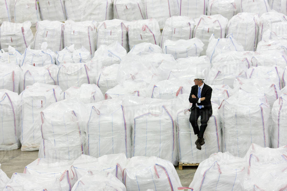 Businessman Sitting On Top Of Large Bags Recycled Plastic Pellets In Warehouse
