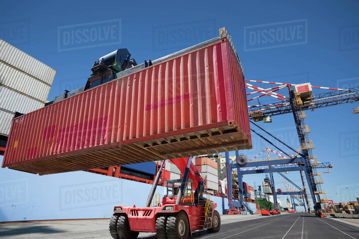 Mobile crane moving cargo container at commercial dock stock photo