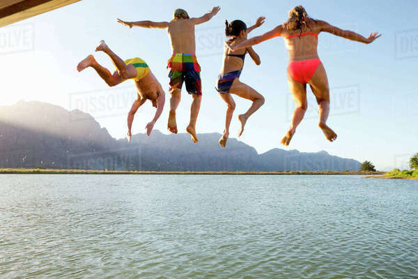 Family, in swimwear, jumping into a lake from a jetty Royalty-free stock photo