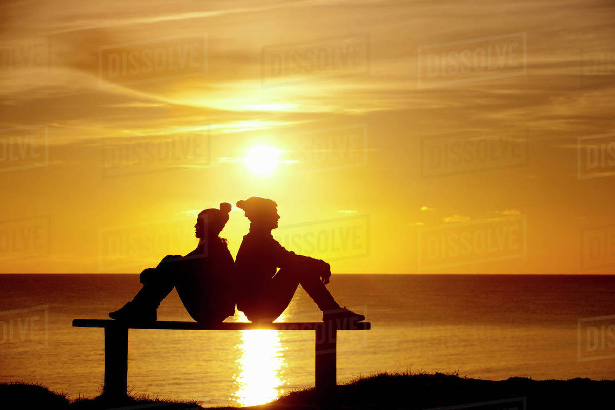 Silhouette of couple, sitting back to back on bench, against sunset ... for bench silhouette back  166kxo