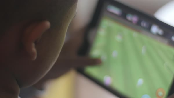 Hand-held shot of a boy playing a soccer game on a tablet Royalty-free stock video