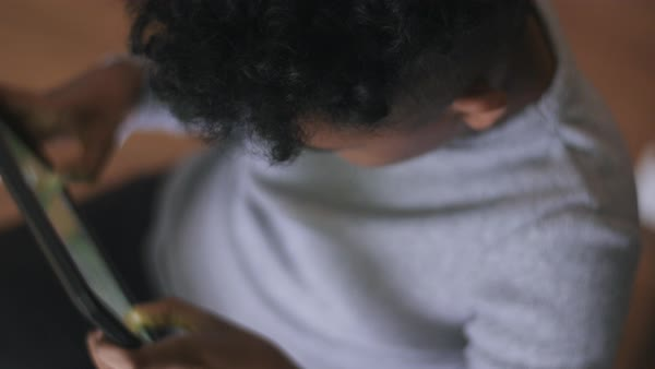 Hand-held shot of a boy playing a game on a tablet Royalty-free stock video