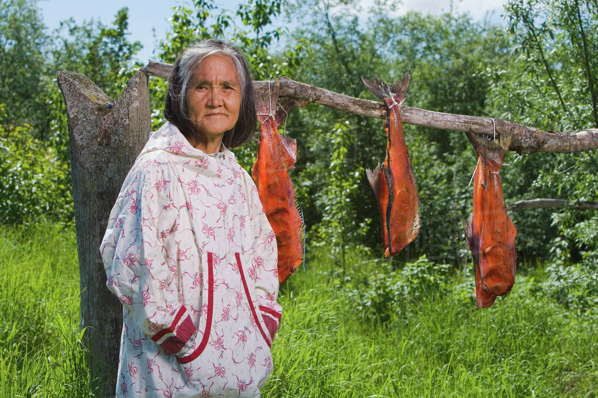 Elder Native Yupik Woman Standing In Front Of Fish Drying Rack at Fish Camp  Akiachak We Alaska Summer stock photo