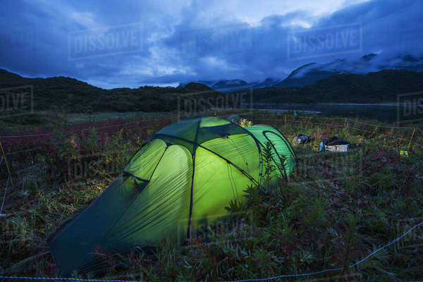 Tent glows at dusk at camp site surrounded by bear protection fence near Kinak Bay along Katmai Coast, Katmai National Park, Southwest Alaska Rights-managed stock photo