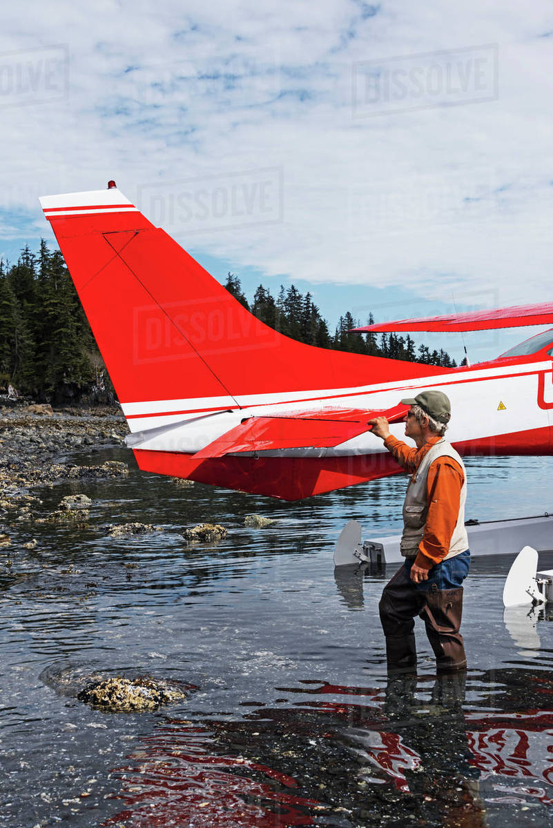 Man standing next to a Cessna 206 float plane in Hobo Bay, Port Wells,  Prince William Sound, Southcentral Alaska, USA stock photo