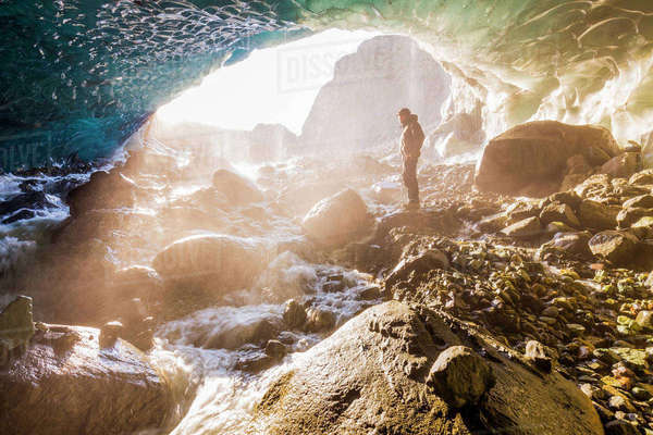 A man stands at the entrance of an ice cave bathed in warm sunlight and mist, Wrangell-St. Elias National Park; Alaska, United States of America Rights-managed stock photo