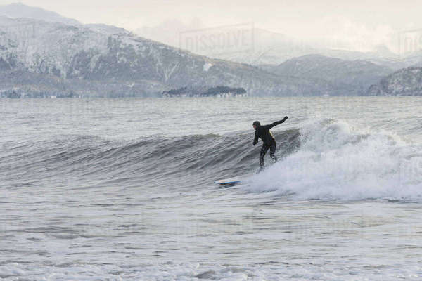 Person surfing in winter in Homer, Kenai Peninsula, Kachemak Bay, Alaska. Rights-managed stock photo