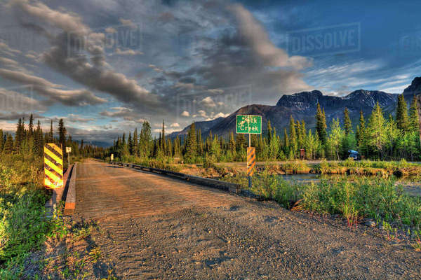 Bridge over Jack Creek on the Nabesna Road with Skookum Volcano at sunset in Wrangell St. Elias National Park and Preserve, Southcentral Alaska, Summer, HDR Rights-managed stock photo
