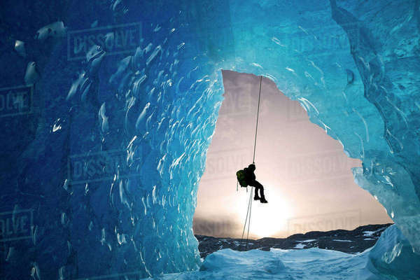 Composite: View From Inside An Ice Cave Of An Iceberg Frozen In Mendenhall Lake As An Ice Climber Rappels Down A Rope, Juneau, Southeast Alaska, Winter Rights-managed stock photo