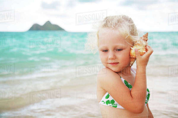 Hawaii, Oahu, Lanikai, Young Girl Listening To A Shell. Rights-managed stock photo