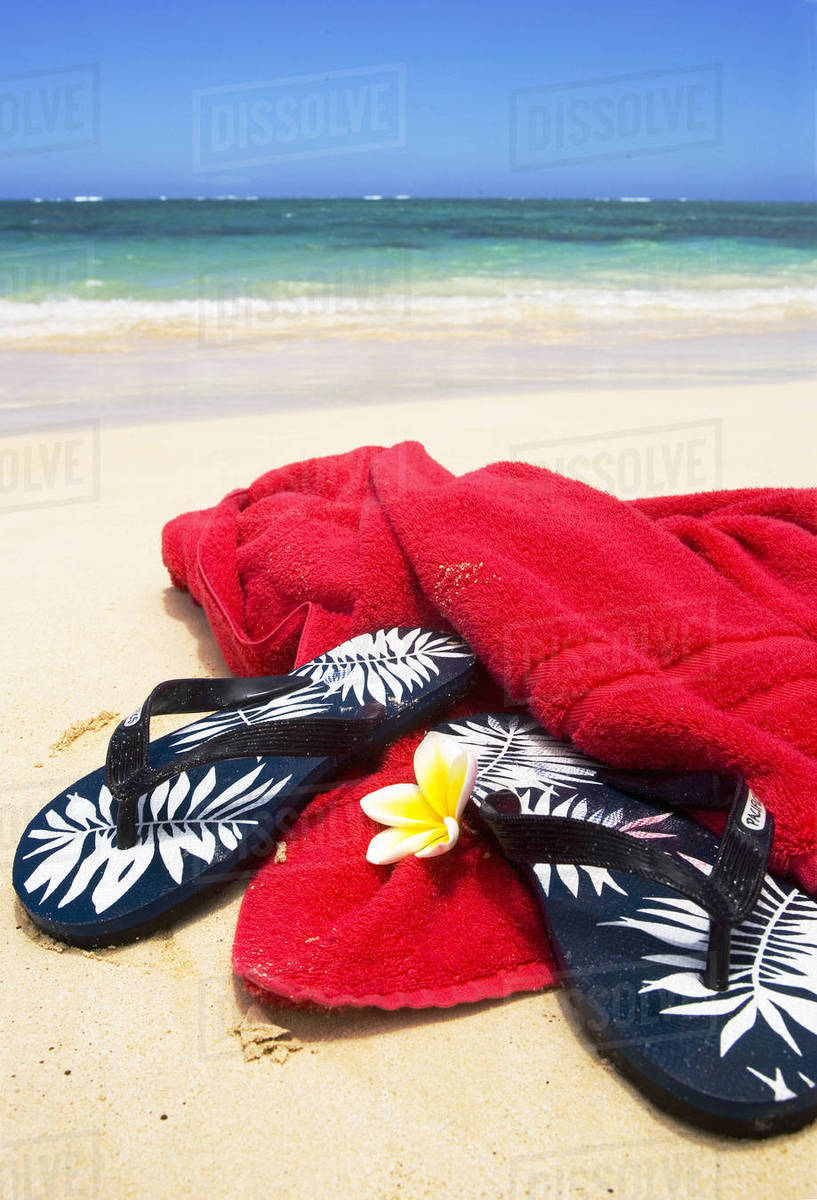 8d5b18f58 Pair Of Flip Flops With Towel And Plumeria On White Sand Beach
