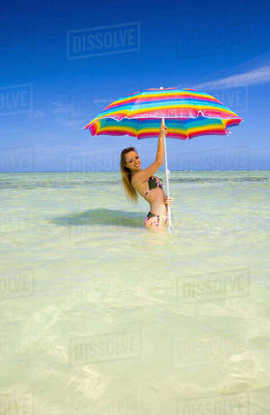 Hawaii, Oahu, Kaneohe, Woman Standing Under A Brightly Colored Umbrella In Crystal Clear Water At The Sandbar Or Dissapearing Island Rights-managed stock photo