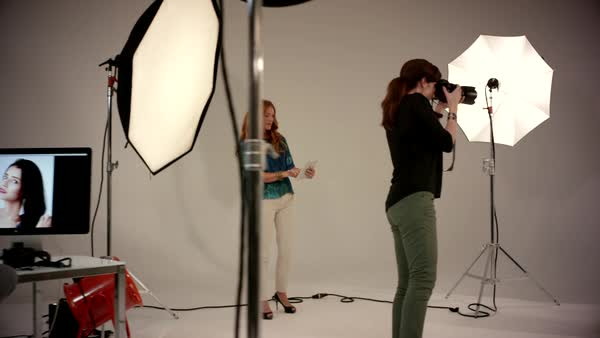 Female photographer photographing fashion model at studio. Royalty-free stock video