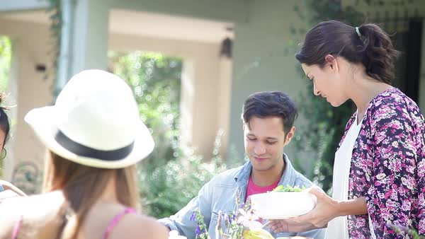 Woman serving her friends at an outdoor dinner party Royalty-free stock video