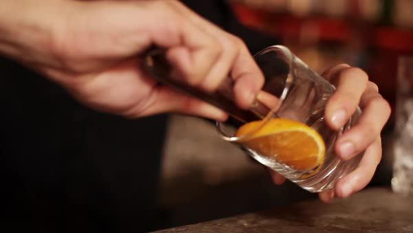 Bartender muddling orange slice Royalty-free stock video