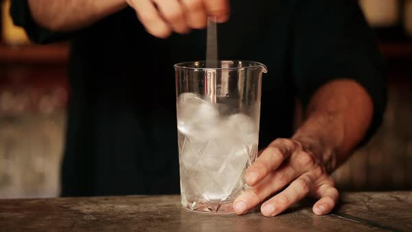 Bartender stirring ice cubes in glass Royalty-free stock video