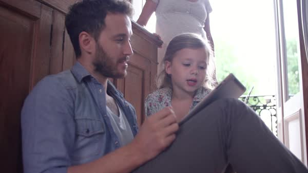 Father and young daughter sitting on the floor, using digital tablet together Royalty-free stock video